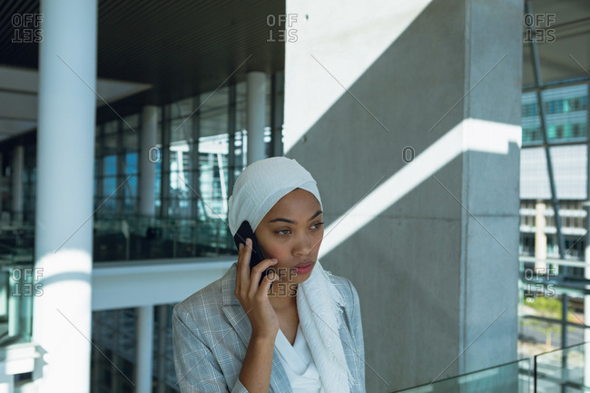 Businesswoman in hijab talking on mobile phone in corridor at modern office