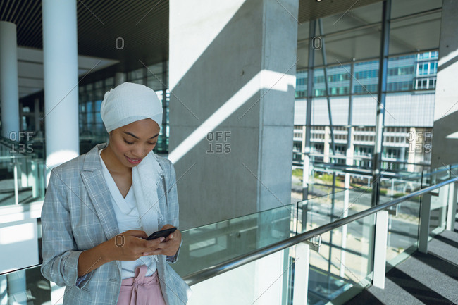 Businesswoman in hijab leaning on railing and using mobile phone in corridor at modern office