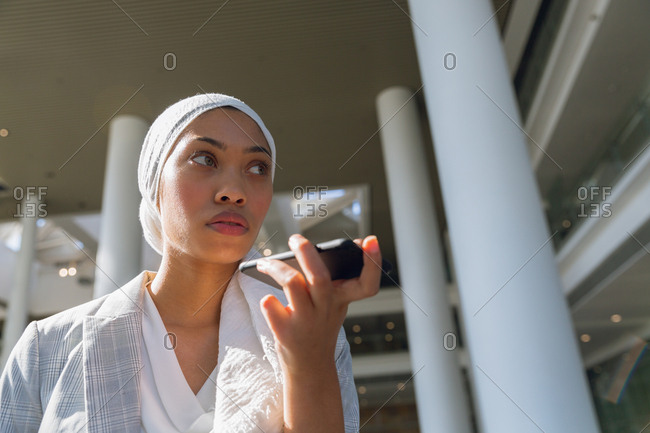 Businesswoman in hijab talking on mobile phone in a modern office