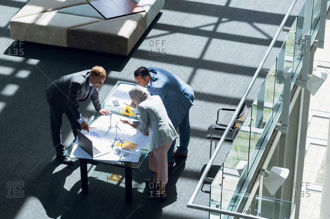 Male and female architects discussing over blueprint in office