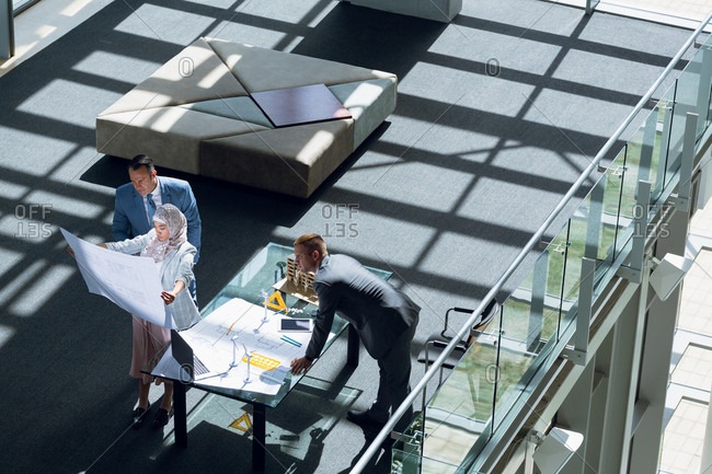 Male and female architects looking at blueprint in office