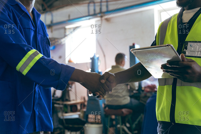 Two men shaking hands and holding a tablet in a sports equipment factory