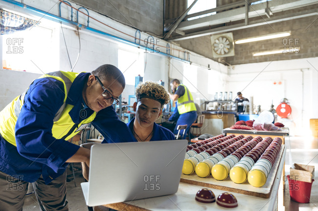 Young men using a laptop in a sports equipment factory
