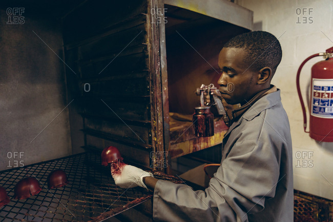Young man working in a sports equipment factory