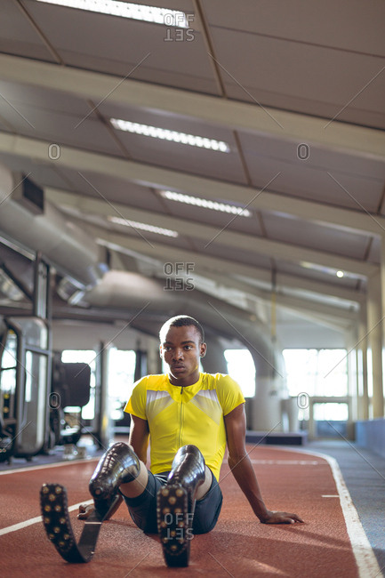Disabled male athletic relaxing on a running track in fitness center