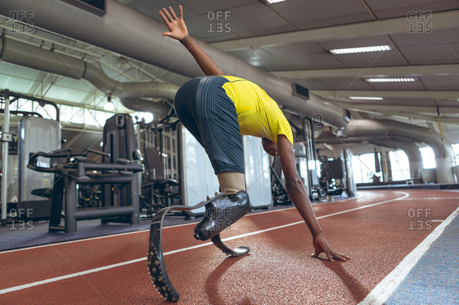 Disabled African American male athletic running on sports track in fitness center