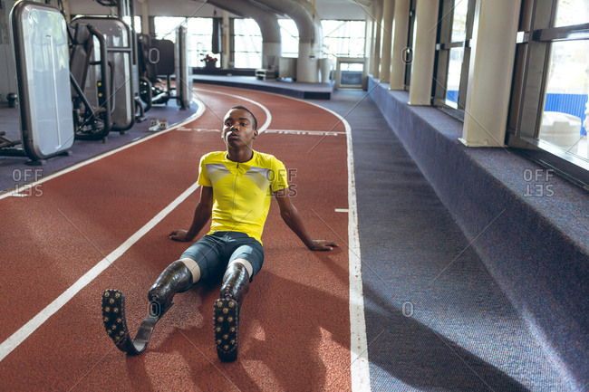 Disabled African American male athletic relaxing on a running track in fitness center