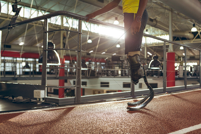 Disabled African American male athletic standing on running track in fitness center
