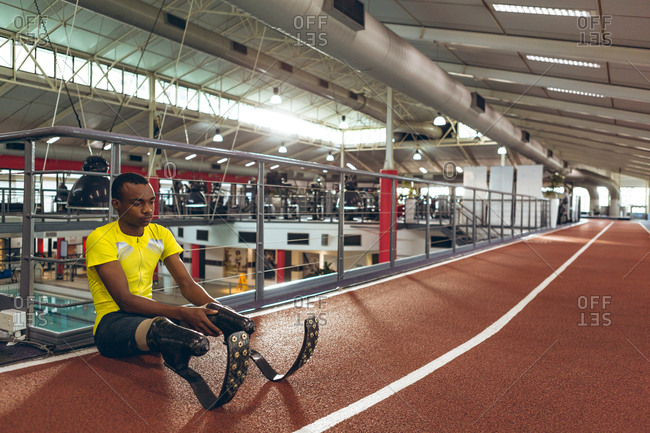Disabled African American male athletic sitting on race track in fitness center