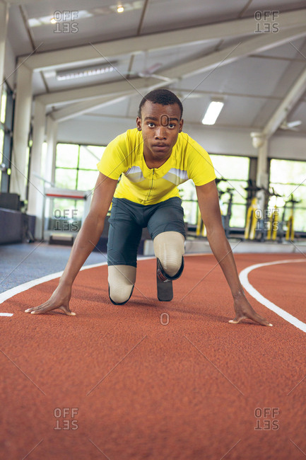 Disabled African American male athletic in starting position on running track in fitness center