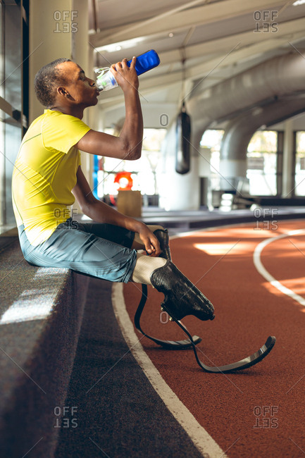 Disabled African American male athletic drinking water on a race track in fitness center