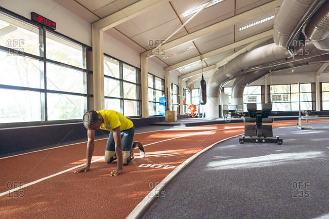 Disabled African American male relaxing on a running track in fitness center