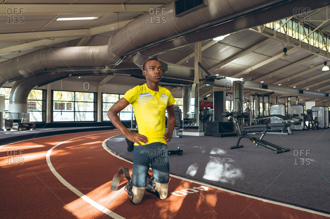 Disabled African American male kneeling with hands on hip in fitness center