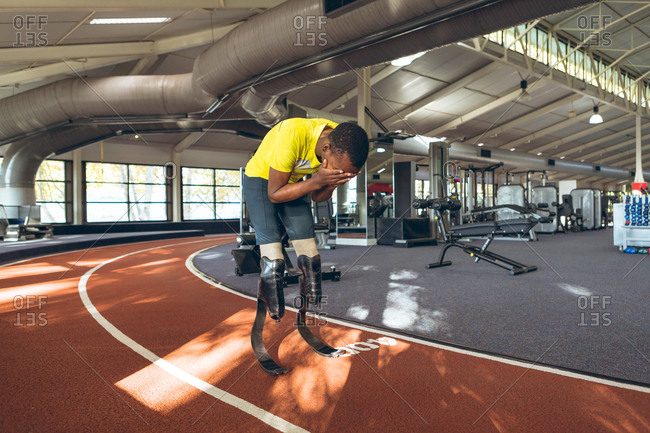 Disabled African American male athletic disappointed after losing race in fitness center