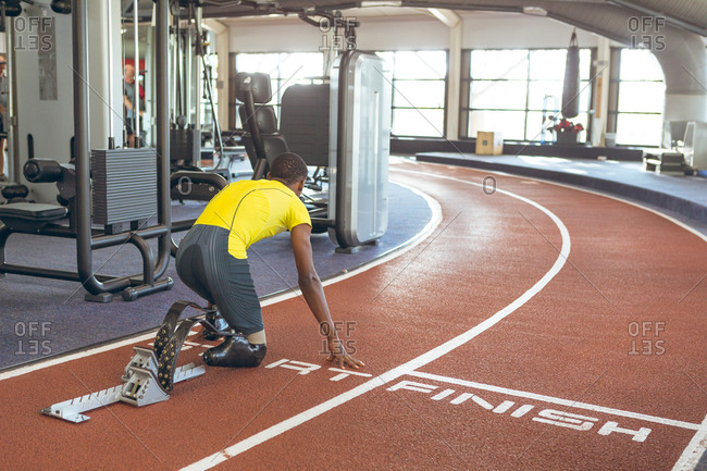Disabled African American male athletic at starting block on running track in fitness center