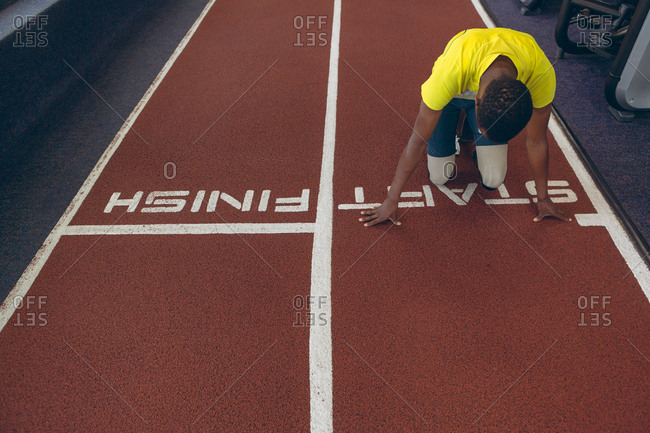 Disabled African American male athletic at starting point on running track in fitness center