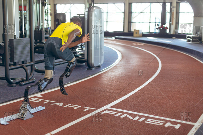 Disabled African American male athletic running on race track in fitness center