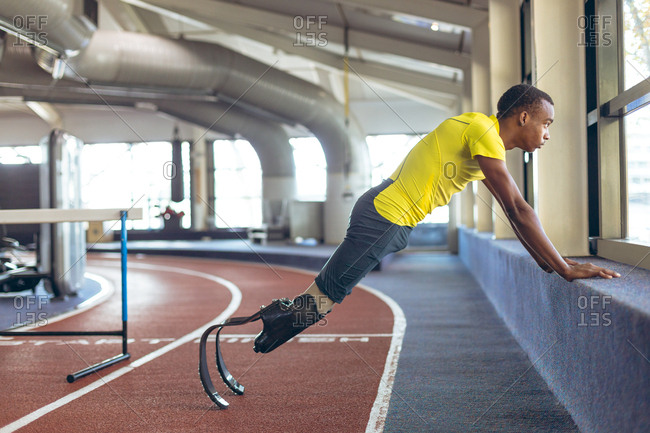 Disabled African American male athletic exercising on running track in fitness center
