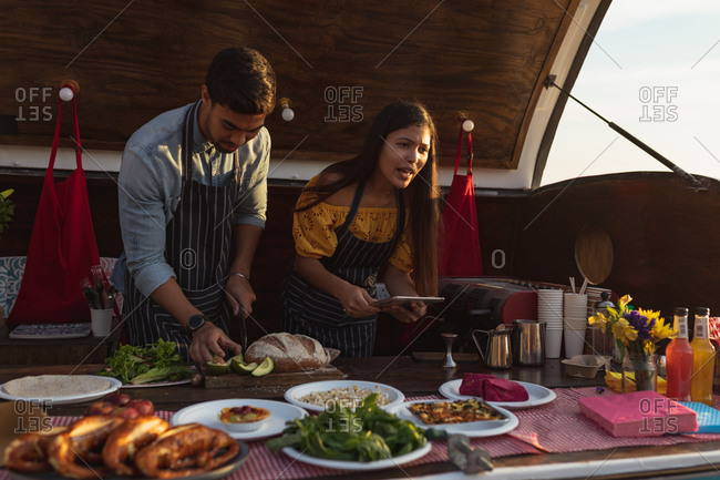 young mixed race couple busy preparing food stall