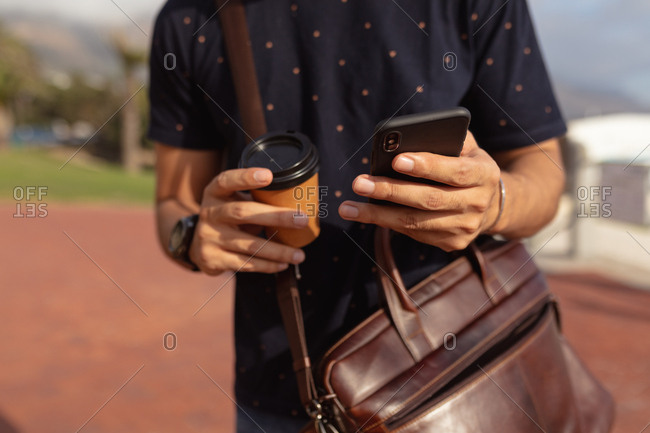 Man wearing a shoulder bag with a coffee and smartphone