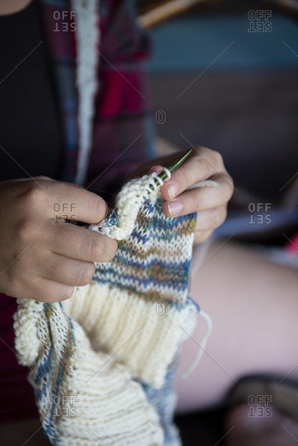 Woman knitting a cream and teal sweater