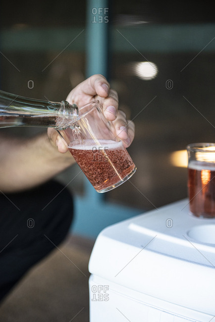 Man pouring sparkling rose wine into a glass