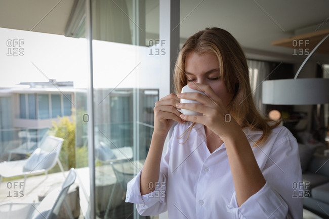 Young blonde woman in an apartment drinking coffee