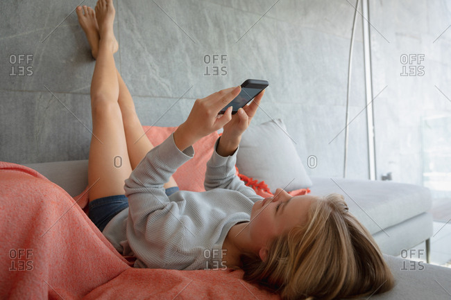 Young blonde woman lying down using smartphone