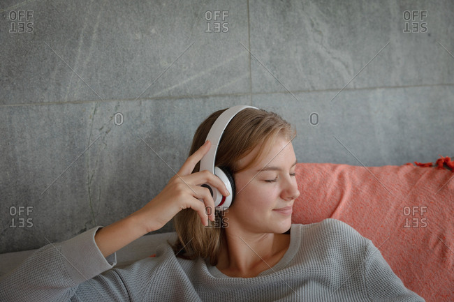 Young blonde woman listening to music with headphones on