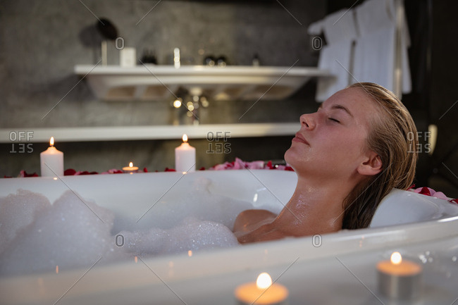 Young blonde woman relaxing in a bath
