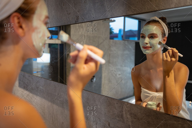 Young woman applying a face mask in a modern bathroom
