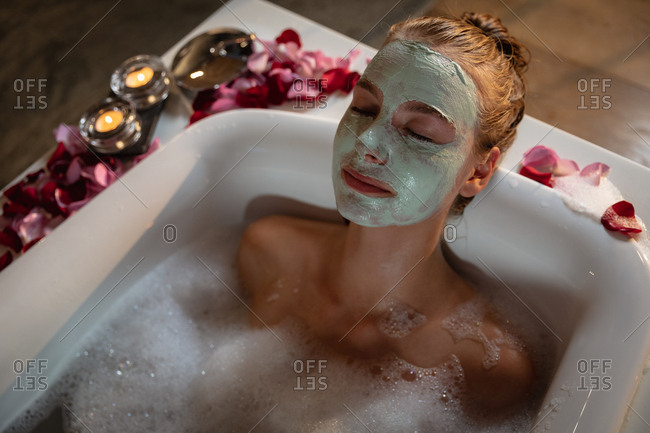 Young blonde woman with face mask relaxing in a bath