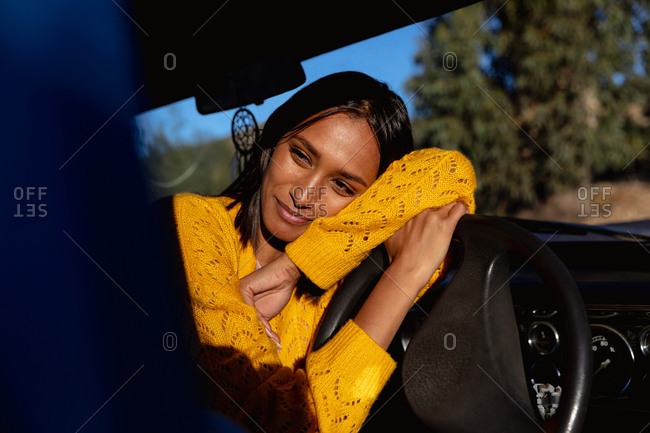 Young woman leaning on steering wheel smiling