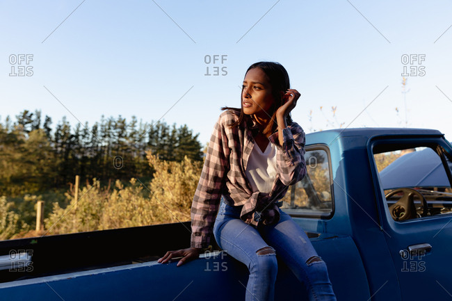 Young woman sitting on a truck at the roadside