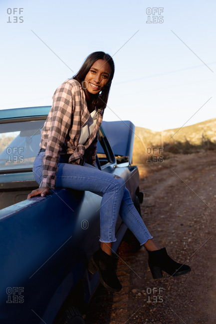 Portrait of young woman sitting on a truck at the roadside