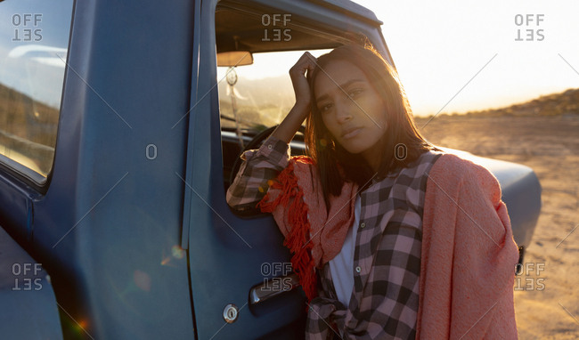 Portrait of a young woman leaning on a pick-up truck during a stop off on a road trip