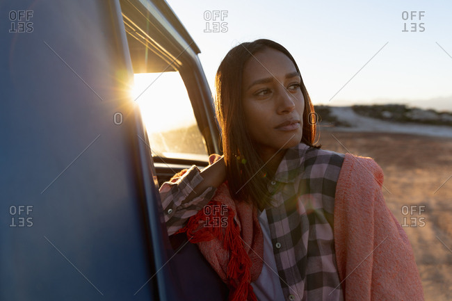 Young woman leaning on a pick-up truck during a stop off on a road trip