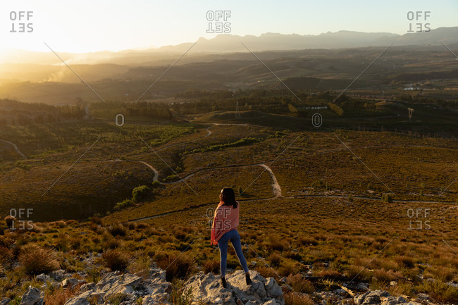 Young woman standing on a rock enjoying the view of the landscape in front of her