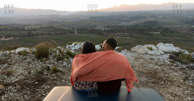 Young couple on a road trip sitting outside on their truck at