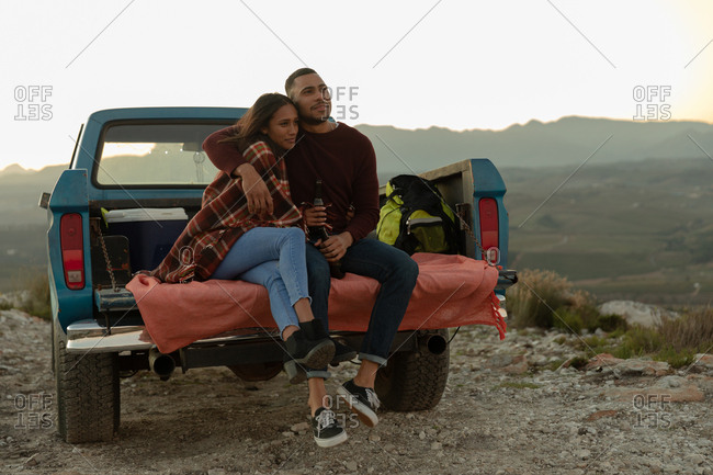 Young couple on a road trip sitting outside on their truck at sundown