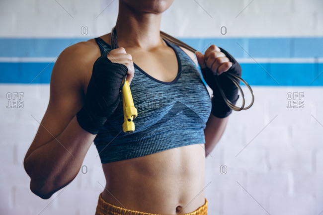 Female boxer standing with skipping rope in boxing club