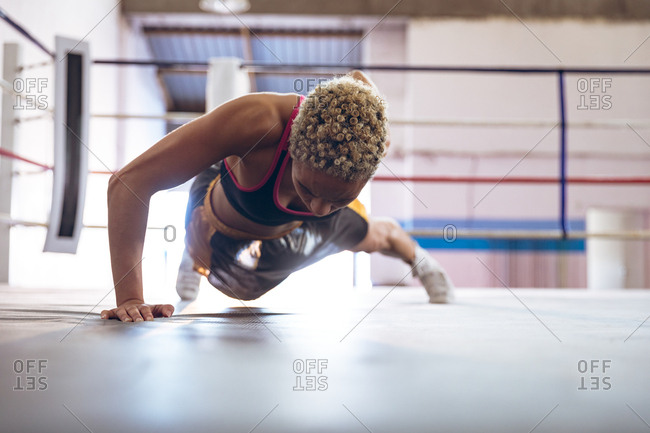 Female boxer exercising in boxing ring at fitness center