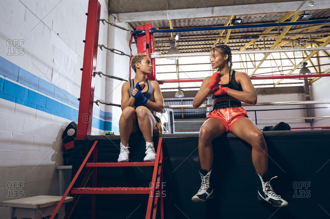 Female boxers talking and wearing hand wrap at boxing club