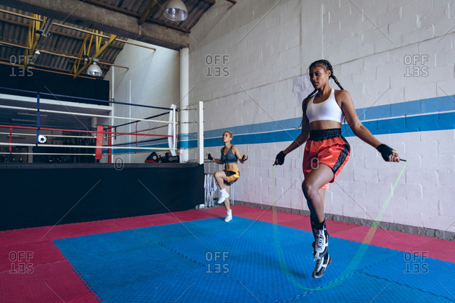 Female boxers exercising with skipping rope in boxing club