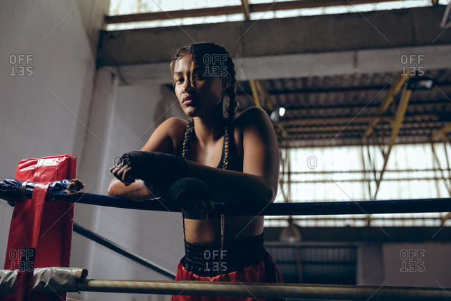 Female boxer leaning on ropes and looking at camera in boxing ring at boxing club