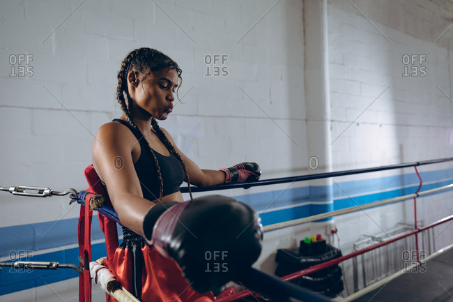 Female boxer resting in the corner of the boxing ring at boxing club
