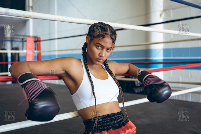 Female boxer with boxing gloves leaning on ropes and looking at camera in boxing ring at boxing club