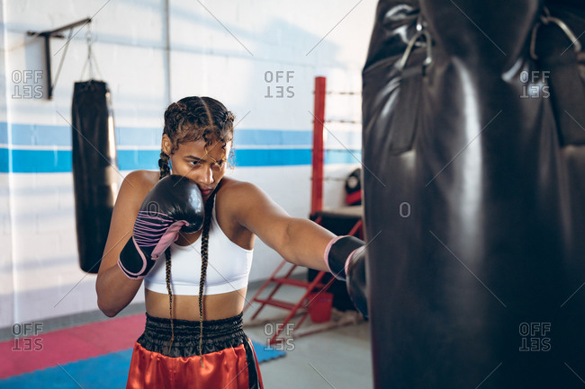 Female boxer practicing boxing with punching bag in boxing club