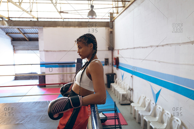 Female boxer taking rest in boxing ring at fitness center