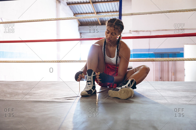 Female boxer tying shoelaces in boxing ring at fitness center
